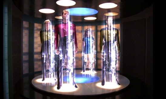 Four people on a transporter pad with vertical beams of light over them