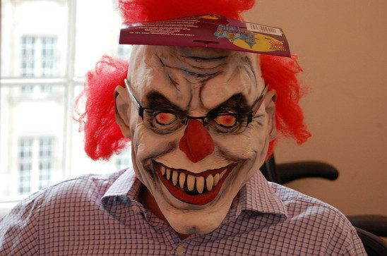 Man in plaid shirt and glasses wearing a clown mask.