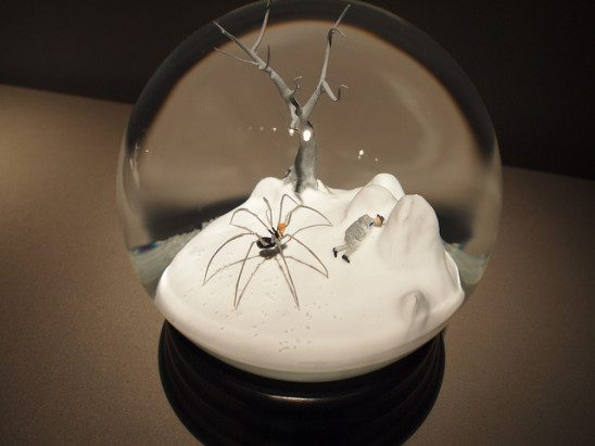 Snow globe with barren tree and giant spider inside.