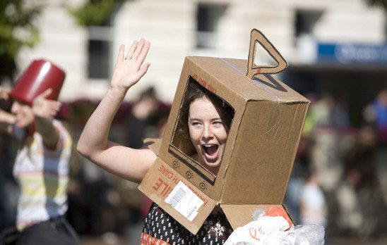 Girl wearing cardboard tv costume.