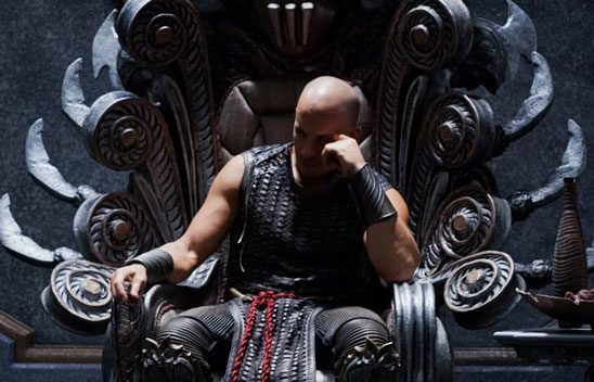 A muscled Riddick broods on his throne.