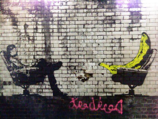 Wall art of a man counseling a giant banana.