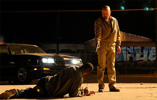 Walter points a gun at a man lying in a parking lot