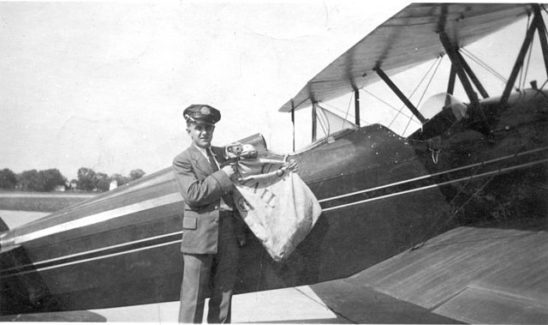 A pilot loading a sack of mail aboard his biplane.