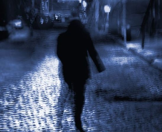 A dark figure on an empty street.
