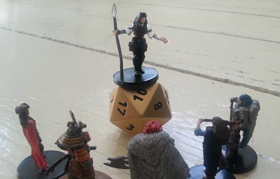 A mini stands atop a large D20, speaking to a crowd