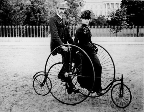 A couple on an old-fashioned bicycle.