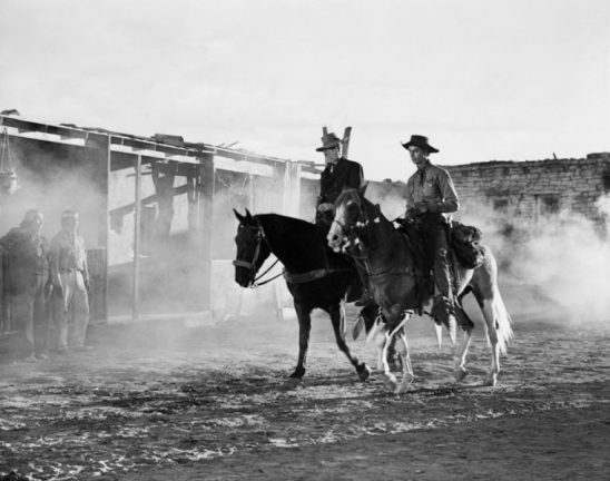 Too men on horseback in a black and white, Old West type setting.