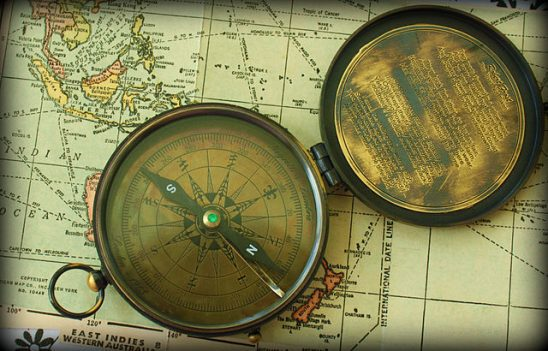 A vintage compass on a vintage map.