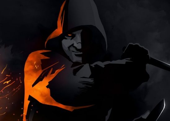 A cloaked man, lit by fire light, with a dagger in one hand.