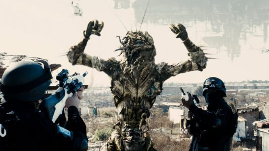An alien being held at gunpoint in District 9.