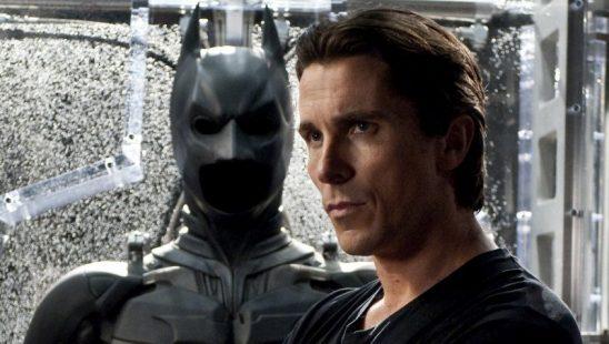 Christian Bale standing beside the Batsuit.