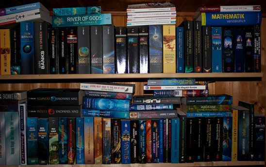 A book shelf full of speculative fiction titles.