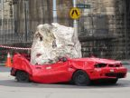 red car that's been crushed by huge rock
