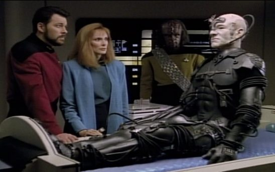 Commander Riker and Dr. Crusher oberve Captain Picard, now a borg