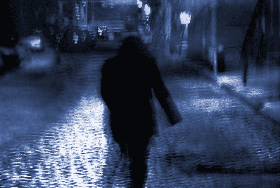 A shadowy man walking down a street from Chronicles of Darkness.