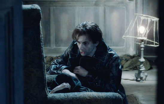 Through a doorway, Barty Crouch Jr kneels by Voldemort's char