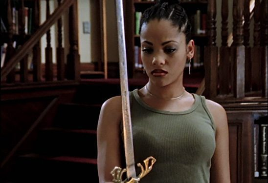 Kendra Young, an athletic black woman, holds a sword