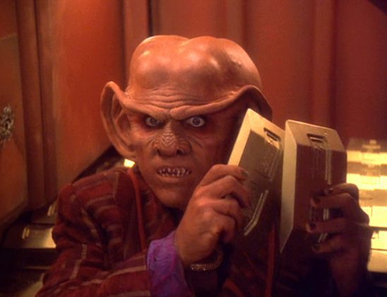 Quark holding two bricks of gold pressed latinum from Deep Space Nine.