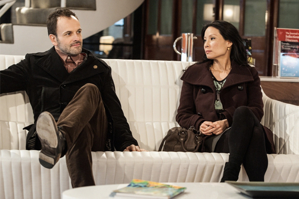 Holmes and Watson from Elementary sit on a couch together.