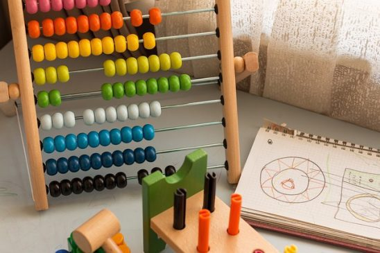 Abacus next to drawings and colorful pegs