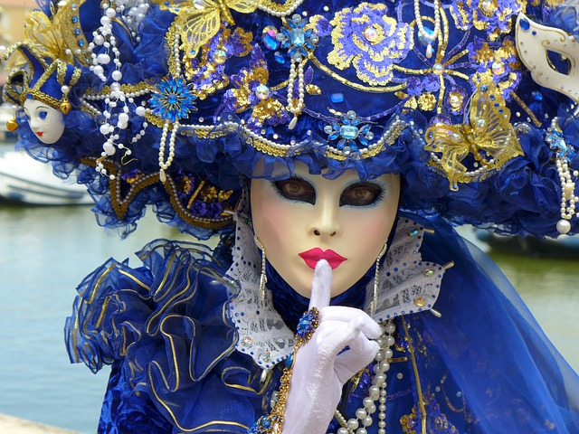 Women in elaborate carnival mask and custom puts a finger to her lips
