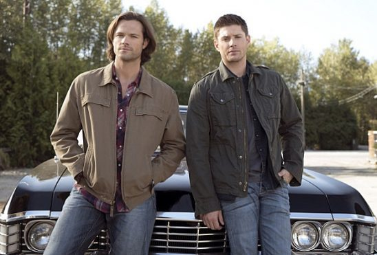 Sam and Dean lean against the hood of a car.