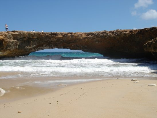 A stone bridge built over a beach.