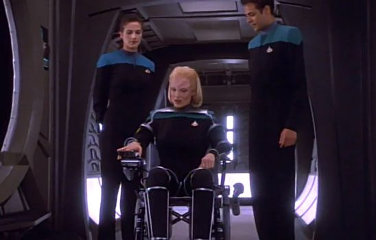 A woman in a wheelchair wearing a star fleet uniform
