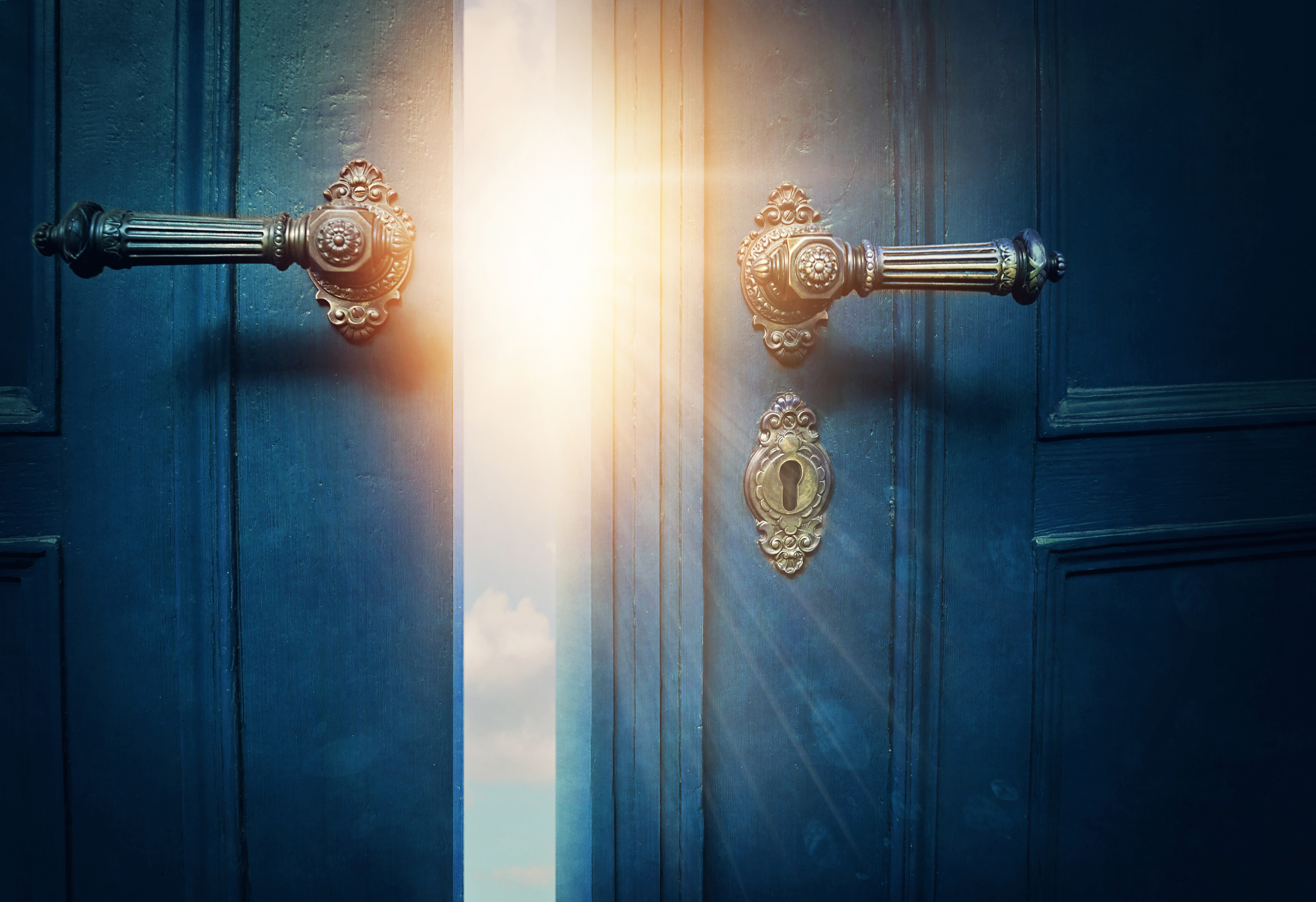 Double doors opening with a bright sky on the other side