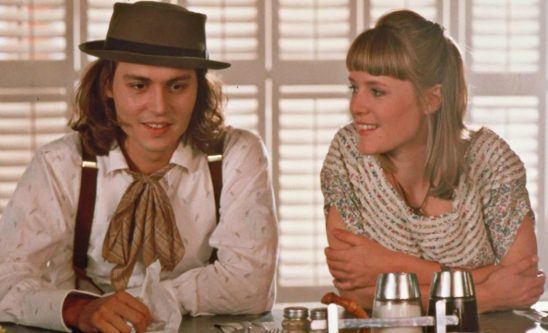 A young white man and woman in quirky clothing sitting next to each other at a diner