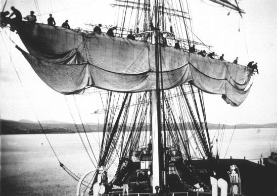 A black and white photo of sailors unfurling the main sail on a barque.
