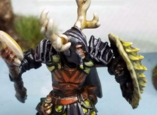 A miniature of a druid wearing a helmet with antlers holds up his shield and axe