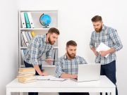 Three identical white men in identical shirts work together