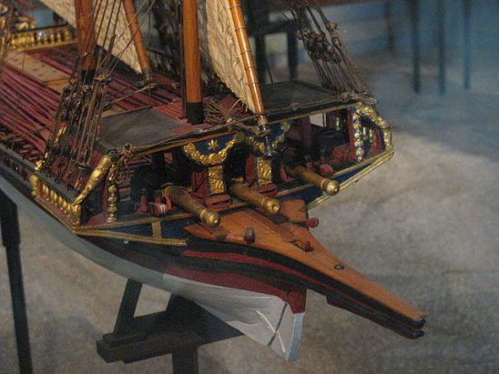 A model of a galley with three guns mounted on the bow.