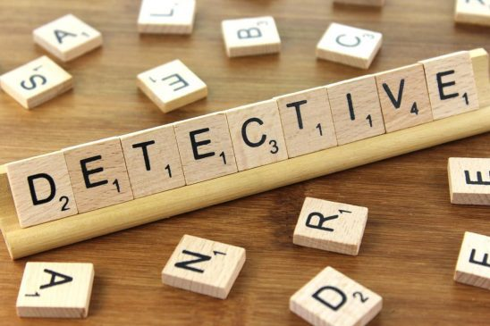 "Scrabble tiles arranged to spell ""detective."""