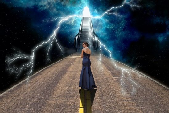 A woman standing in front of a stairway going into the clouds.