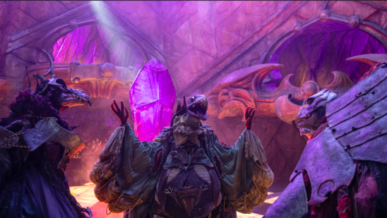 Several Skeksis standing in front of the crystal.