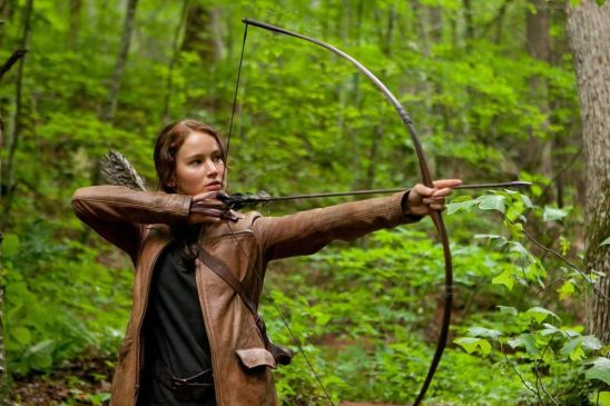 Katniss drawing an arrow with her bow.