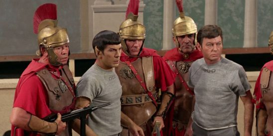 Spock and McCoy held captive by Romans with machine guns.