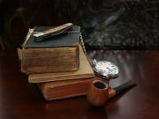 Several old books with a pipe, compass, and knife