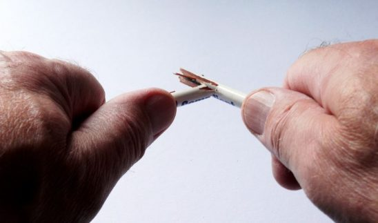 Two hands breaking a pencil
