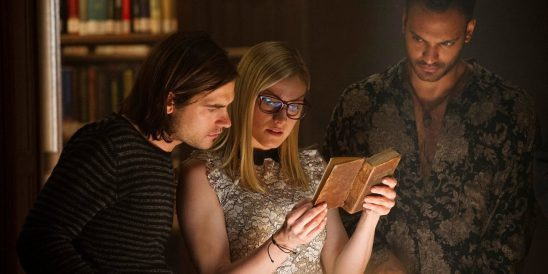 Three characters looking at a book from The Magicians.