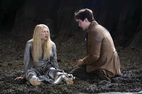 Tristan finds a blond woman wearing a silver dress lying in a crater