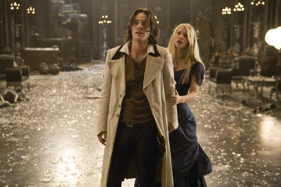 Tristan and Evane stand in a great hall full of shattered glass, they look frightened