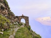 An ancient arch over a path on a slope