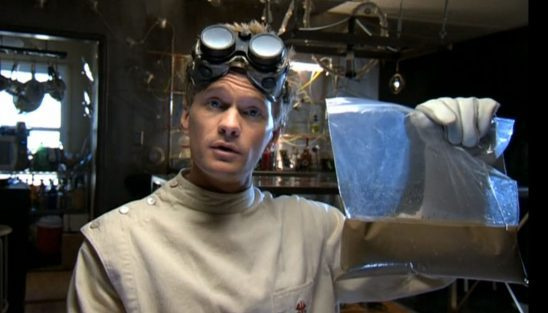 Dr. Horrible holds up a bag of supposed gold bars that have dissolved into mush.