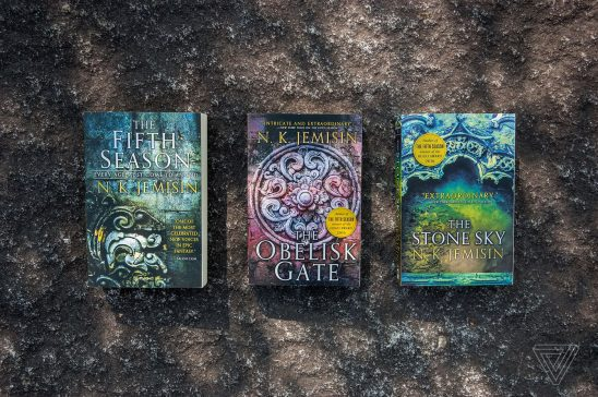 The three novels of the Broken Earth series laid out on stone.