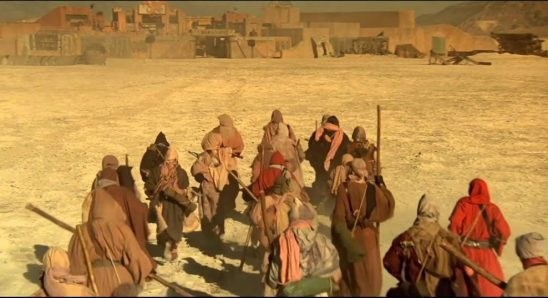 Robed soldiers headed towards a dilapidated settlement.