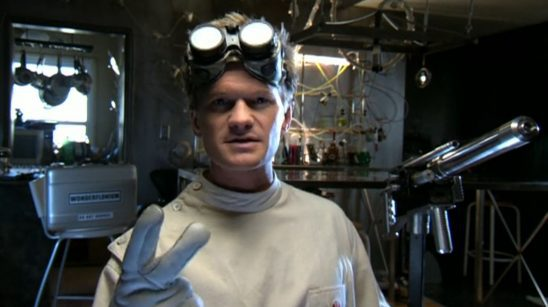 Dr. Horrible speaks to followers with the wonderflonium and his freeze ray behind him